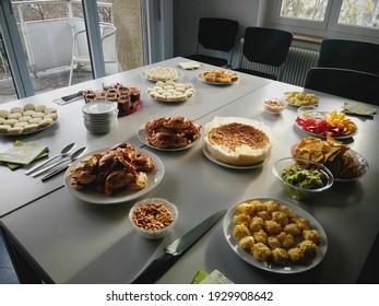 Office apero with international food, empanadas, quiche, vegetables, alfajores.