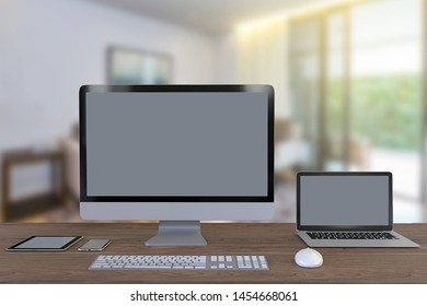 Office appliances blank screen for mokeup and advertising contents on blur livngroom background. Computer notebook and mobile phone on wooden table.