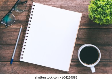 Office atable with blank notebook and laptop  /  Coffee cup