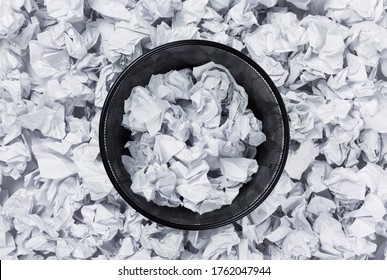 Office black garbage basket full stands among crumpled paper, top view