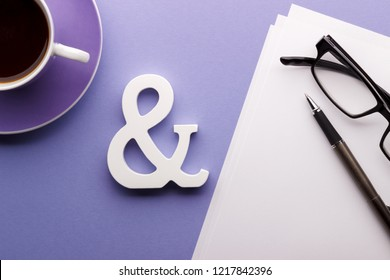 Office or bloger's desk coffee glasses pen paper lilac backgound