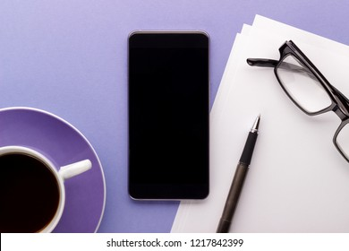 Office or blogger's desk smartphone coffee glasses pen paper lilac background top view