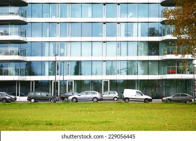 office building or apartment house with cars parking front of it