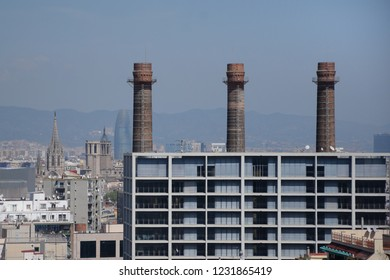 Office building in Barcelona city and old factory chimneys.