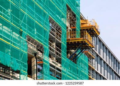 office building construction with scaffolding and green net
