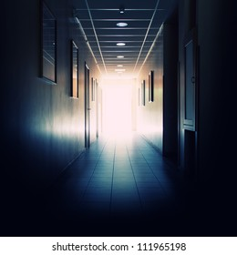 Office building corridor with light at the end