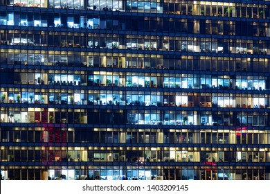 Office building exterior in the late evening with interior lights. Business people working in the evening. Illuminated office building