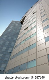 Office building with a hinged facade. Part of the facade opaque aluminum panel, part of - a complete glazing. Against the background of blue sky. Vertical orientation.