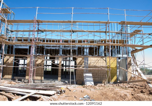 An office building in its phase of construction shows the intricate scaffolding required to erect the structure.