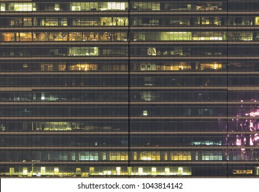 office building side view. People working during night in modern glass wall facade modern tower.