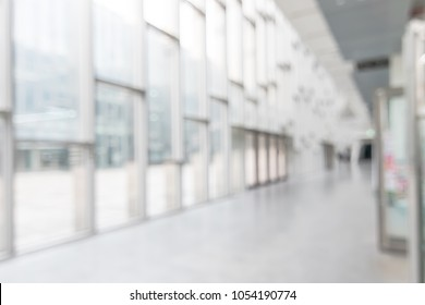 Office building or university lobby hall blur background with blurry school hallway corridor interior view toward empty corridor entrance, glass curtain wall, floor and exterior light illumination