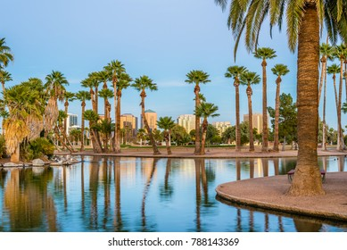 Office buildings in Phoenix, viewed from across the lagoon in Encanto Park, glow gold in the rays of the setting sun.