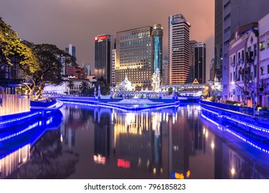 Office buildings reflect in the water of the Klang river in front of the Jamek mosque  in the heart of Kuala Lumpur in Malaysia at night. The city is an important center for Islamic finance.