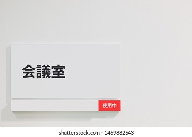 "Office / Business concept : Meeting room sign (occupied) on White wall .Translation:  ""会議室"" is ""Meeting room"" 使用中"" is ""occupied"" in Japanese."
