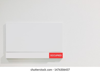 Office / Business concept : Office room sign OCCUPIED on White wall .