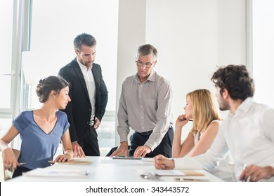 Office business meeting. The team is sitting at a table in a luminous white open space The men are wearing suits and shirts. The senior grey haired boss is up and comparing a new design on his tablet