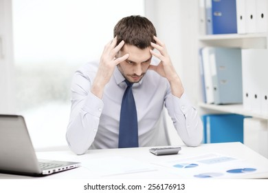 office, business, technology, finances and internet concept - stressed businessman with laptop computer and documents at office