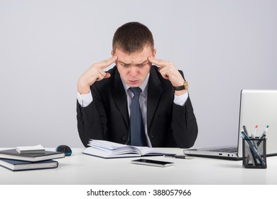 Office, business, technology, finances and internet concept-Frustrated young businessman working on laptop computer at office