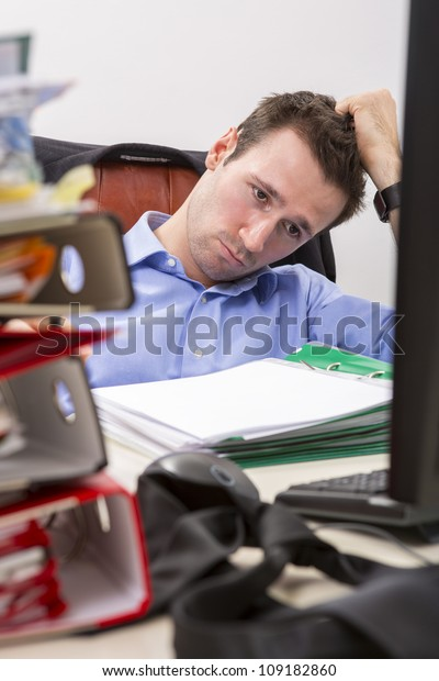 Office businessman at his desk full of documents, showing an overwhelmed expression.