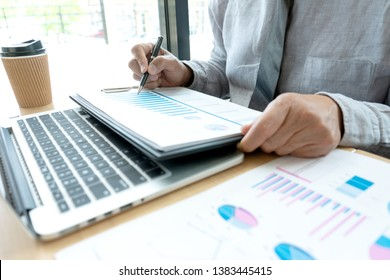 In office businessman in meeting analyses chart graphy marketing plan in business financial  audit project. Or Business adviser analyzing Budget,