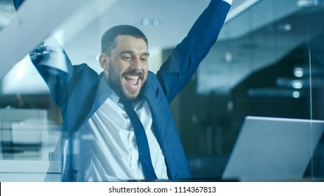 In the Office Businessman Sitting at the Desk Using Laptop Finishes Project and Wins Big. Makes Successful Gestures Raises Arms in Celebration.