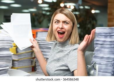 Bürogeschäftsfrau an ihrem Schreibtisch voller Dokumente, die einen überwältigenden Ausdruck zeigen