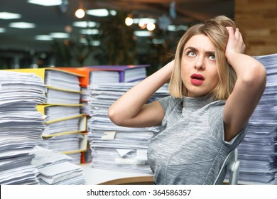 Office businesswoman at her desk full of documents, showing an overwhelmed expression