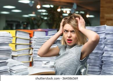 Bürogeschäftsfrau an ihrem Schreibtisch voller Dokumente, die einen überwältigten Ausdruck zeigen