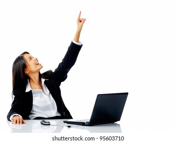 Office businesswoman pointing upward while sitting at her desk, isolated on white