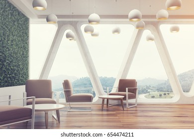 Office cafe interior with a large grass wall, panoramic windows with triangular frames, white round tables and soft brown chairs near them. 3d rendering toned image
