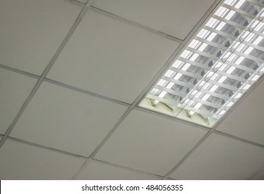 office ceiling. Office ceiling with white fluorescent fixture near window. fluorescent lamp on the modern ceiling. Lights from ceiling. lamp on the modern ceiling. Ceiling detail with a lamps,