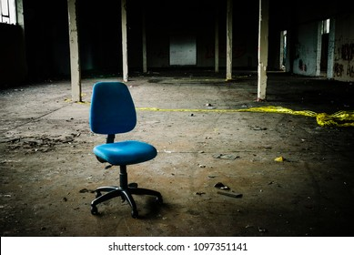 Office chair sits in the middle of an empty, abandoned warehouse.