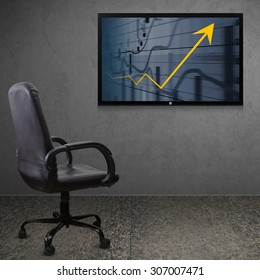 Office chair and TV screen with business graph