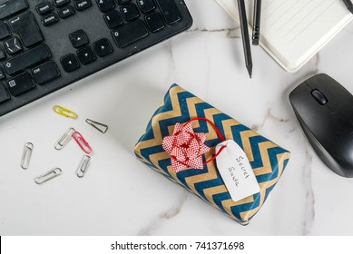 Office Christmas celebration concept, the idea of sharing gifts secret Santa. Keyboard, mouse, notebook, pens, pencils, Christmas gift. White office table, copy space top view