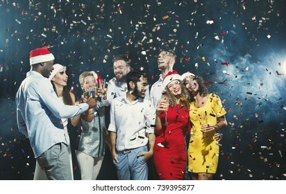 Office christmas party. Group of joyful colleagues having fun at new year celebration. Happy smiling young people drinking champagne and enjoying life.