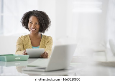 An office in the city. Business. A woman sitting at a desk. Digital tablet and laptop, and green files.