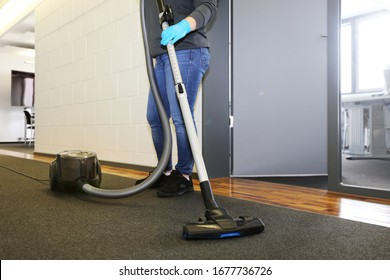Office cleaning: Cleaner vacuums the corridor of an office