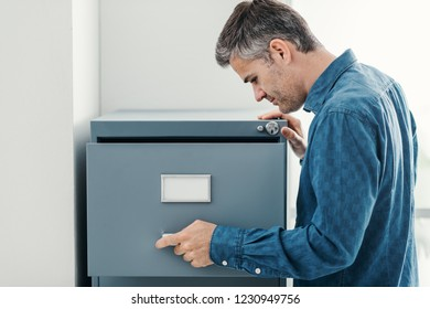 Office clerk searching files in the filing cabinet, he is looking into the file drawer