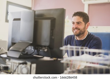 office clerk at work, writing at computer smiling