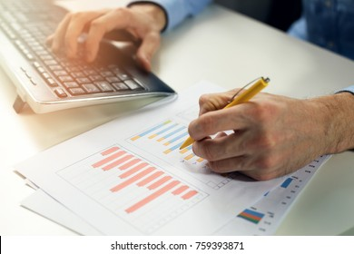 office clerk working with statistical reports and entering data into a computer