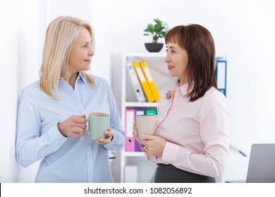 Office coffee break. Two female colleagues with cups of coffee talking in offise.