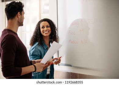 Office colleagues planning and discussing monthly budget on a whiteboard. Smiling businesswoman writing on the board while her colleague holds a paper in hand.
