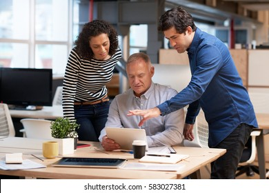 Office colleagues talking business together over a digital tablet
