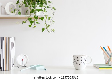 Office creative desk with coffee supplies and white wall.