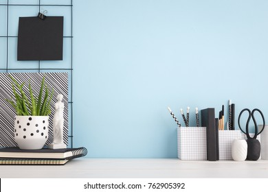Photo of Office creative desk with supplies, and blue wall.