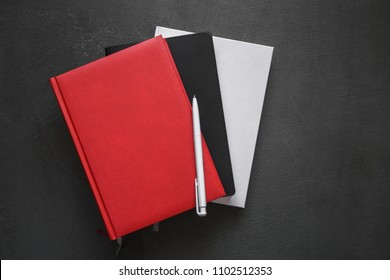 Office dark table. Mock up book blank black, red, white, leather cover for magazine, booklet, brochure, diary, business portfolio mock-up design template on black  background. Flat lay, top view, copy