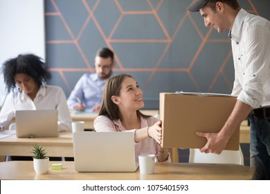 Office delivery service concept, millennial woman receiving box from courier holding package delivering to customer at work, smiling employee or happy worker accepting postal parcel at workplace