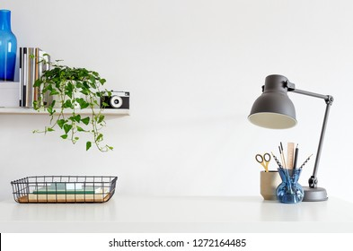 Office desk with boxes, supplies, notebooks, camera, stylish designed lamp and white wall for mock up or copy space.