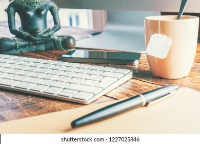 Office desk close-up with keyboard and a cup of tea. Work office concept.