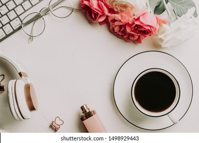 Office desk with computer, cup of coffee, pink rose flowers, headphones, notepad paper blank. Modern minimalist business blog template. Flat lay. Top view. Copy space.